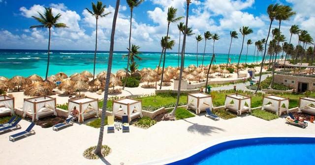praia de punta cana com coqueiros, piscina e camas balinesas