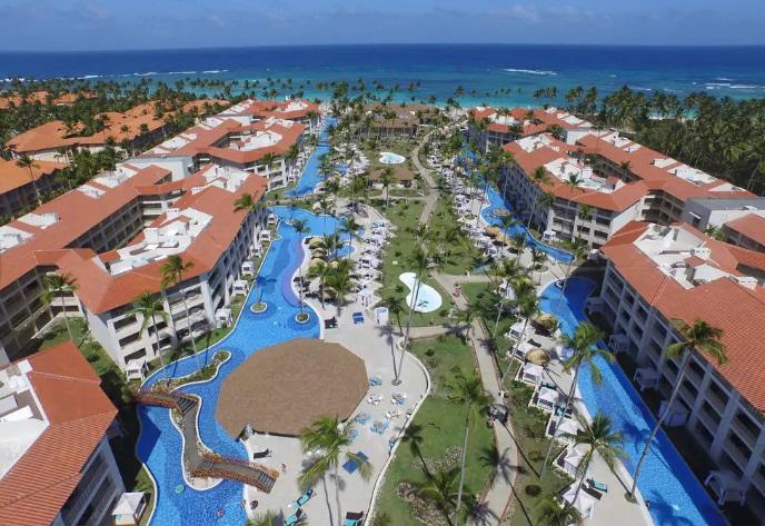mar azul, piscina azul, grama verde, coqueiros e prédios