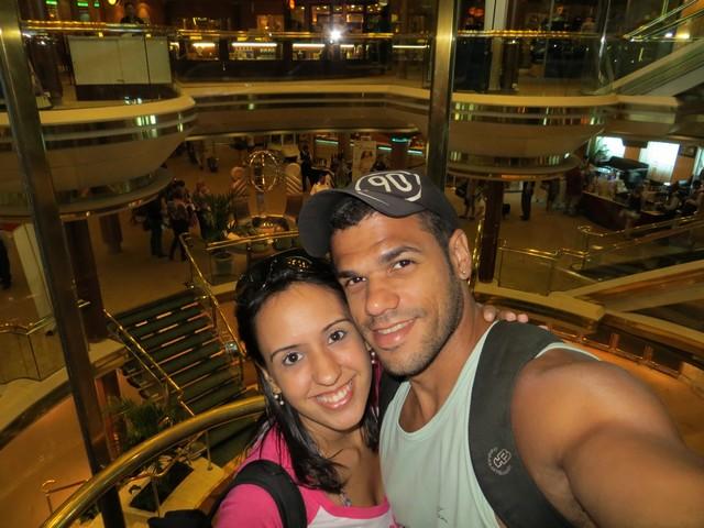 casal no centro do navio com escadas e elevadores panorâmicos