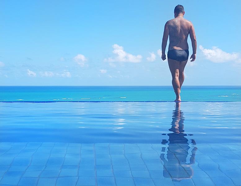 piscina de borada infinita e mar azul na pousada do alto