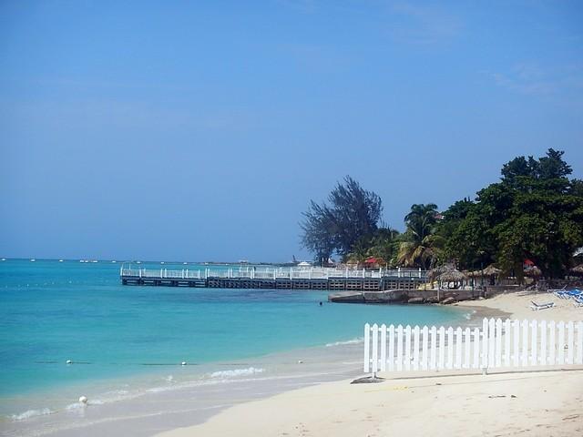 areia branca céu azul sem nuvens cerca branca mar azul turquesa árvores verdes