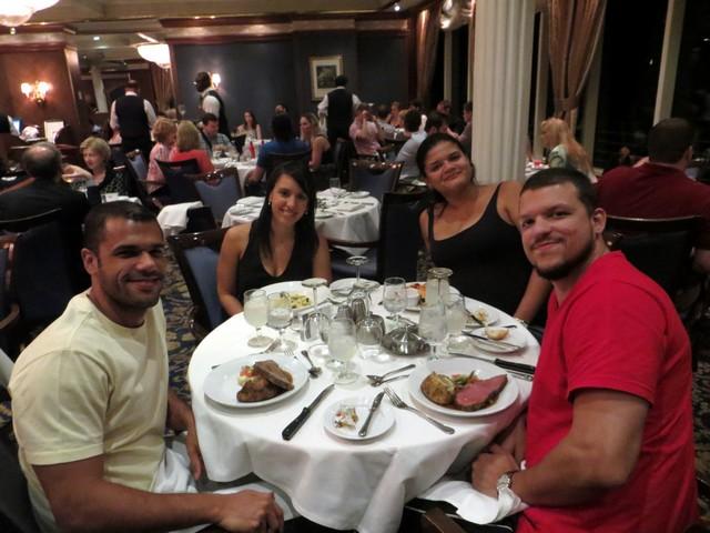 mulheres e homens mesa redonda comida talheres