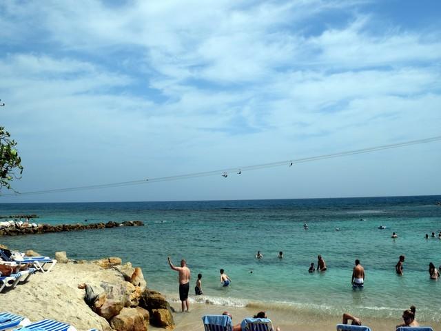 pedras pessoas na água calma céu azul com nuvens tirolesa