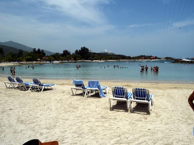 praia areia branca mar calmo espreguiçadeiras tirolesa pessoas na água céu azul poucas nuvens navio ao fundo