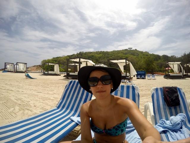 mulher óculos escuros sentada espreguiçadeira camas balinesas praia areia amarelada céu azul com nuvens luz do sol