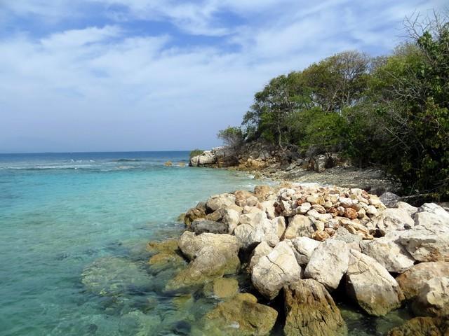 pedras água azul cristalina vegetação céu azul nuvens brancas