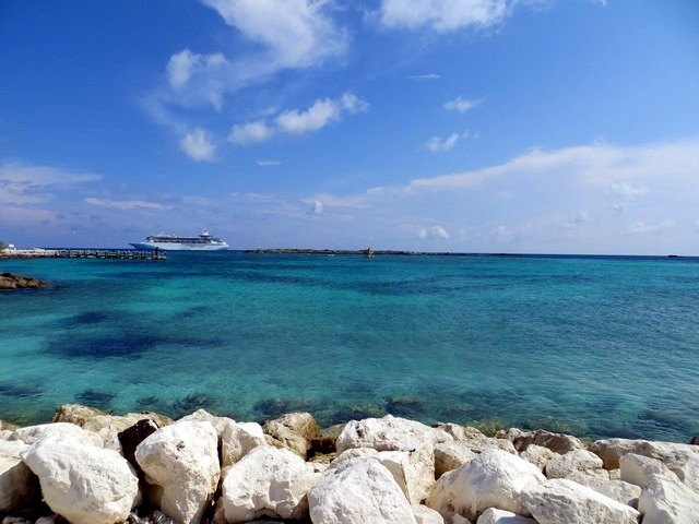céu azul, poucas nuvens, mar cristalino, pedras brancas, navio atracado, cococay