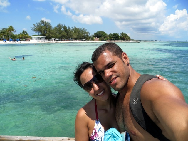 céu azul com poucas nuvens, casal abraçado, mar azul cristalino, algumas árvores na areia