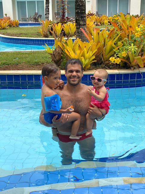 piscina com água azul, plantas verdes, pai com crianças no colo em roupa de banho