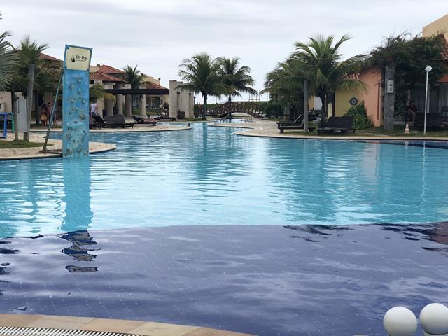 piscina azul com parede de escalada céu nublado e coqueiros