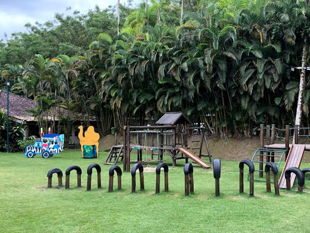 área externa com brinquedos de madeira, gramados, árvores, escorrega, miniclube do portobello