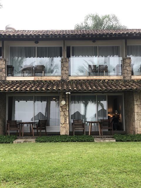 grama verde, varandas com mesas e cadeiras no portobello resort